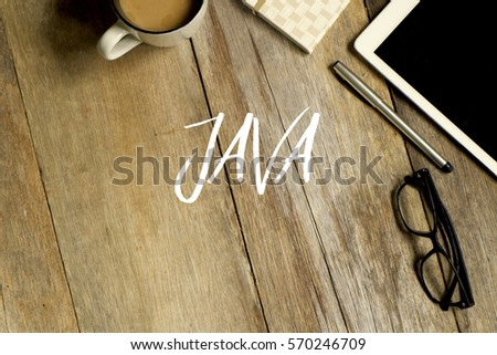 Business concept. Top view of tablet, glasses. notebook pen and a cup of coffee with JAVA written on wooden background. #570246709