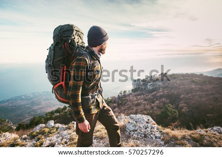 Man traveling with backpack hiking in mountains Travel Lifestyle success concept adventure active vacations outdoor mountaineering sport plaid shirt hipster clothing Royalty-Free Stock Photo #570257296