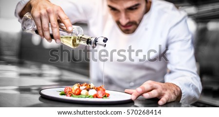 Handsome chef pouring olive oil on meal in a commercial kitchen Royalty-Free Stock Photo #570268414