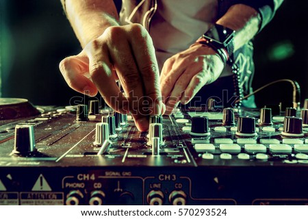 DJ playing music at mixer closeup Royalty-Free Stock Photo #570293524
