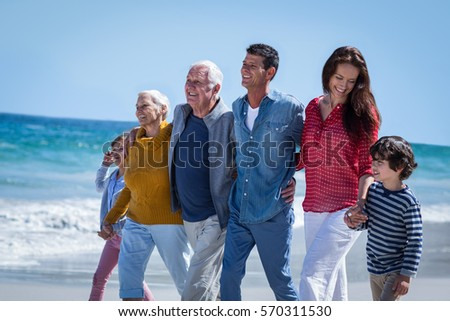 Happy family walking together at the beach #570311530