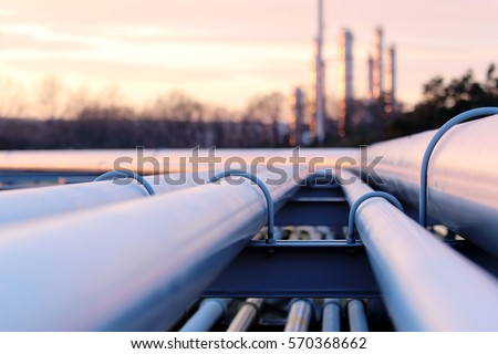 steel long pipes in crude oil factory during sunset Royalty-Free Stock Photo #570368662