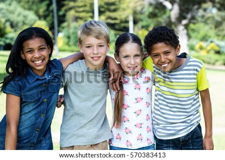 Portrait of happy children standing together in park on a sunny day #570383413