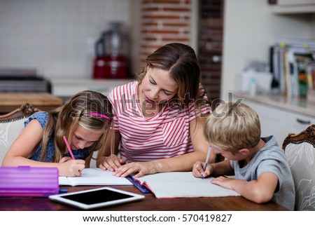 Mother helping kids with their homework at home #570419827