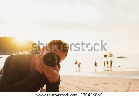 professional photographer takes a picture at sunset on a tropical beach. He is looking at the camera in the backlight.