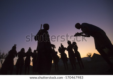 EPUPA, NAMIBIA - CIRCA AUGUST 2016 - Himba villagers gather at dusk to perform a trditional dance. This dance allows visitor to see their culture while providing an income. #570467983