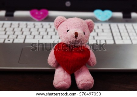 Pink bear red heart love for gift and valentine on keyboard background.
