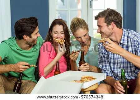 Smiling happy friends eating pizza in party at home #570574348