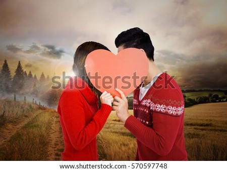Digital image of couple holding heart with a countryside background #570597748