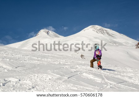 Snowboarder stands and walks on mountain slopes of an extinct volcano Elbrus #570606178