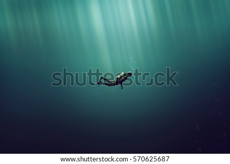 Diver in the deep sea Royalty-Free Stock Photo #570625687
