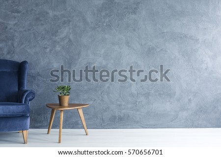 Interior with grey wall blue armchair and wood side table Royalty-Free Stock Photo #570656701