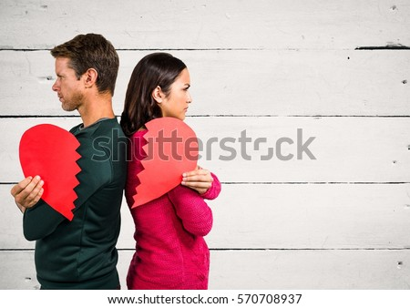Angry couple holding broken heart against wooden background #570708937