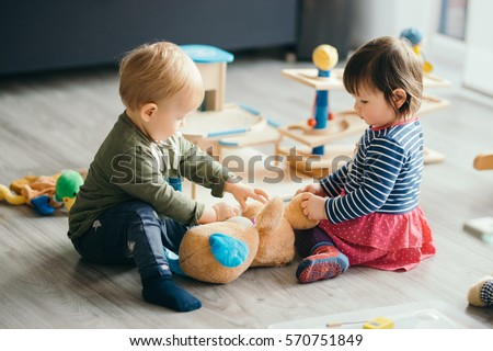 cute little girl and boy playing with toys by the home Royalty-Free Stock Photo #570751849