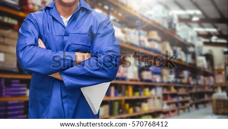 Mid section of supervisor standing with arms crossed in warehouse #570768412