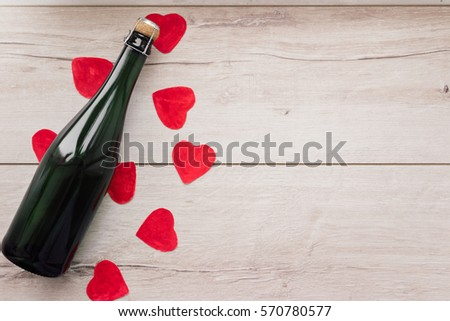 Gift , the heart and the bottle of red wine for a romantic holiday Valentine's day on vintage wooden background.selective focus. #570780577