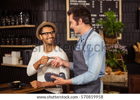Man paying his coffee in a coffee shop #570819958
