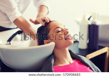 beauty and people concept - happy young woman with hairdresser washing head at hair salon Royalty-Free Stock Photo #570908683