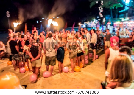 Blur Background of Tourism Hang over at full moon party, Phangan Thailand. People Gathering around the fire, breaker activities game ,  team building