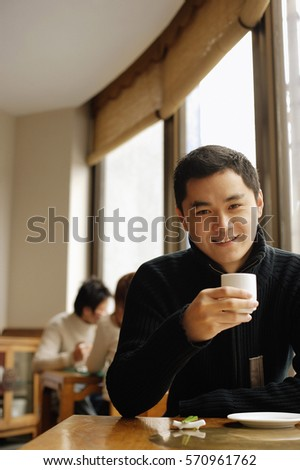Young man sitting at table holding teacup, looking at camera #570961762