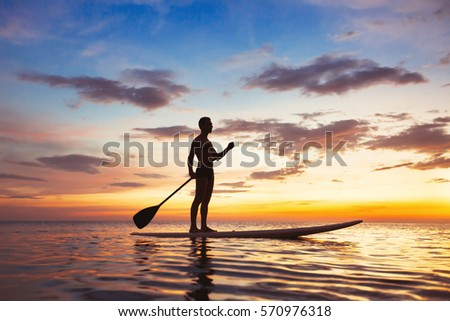paddle standing board, beach leisure activity, beautiful silhouette of man at sunset #570976318