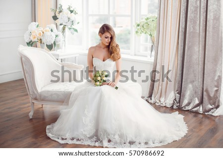 Wedding. Bride in beautiful dress sitting on sofa indoors in white studio interior like at home. Trendy wedding style shot in full length. Young attractive caucasian brunette model like a bride Royalty-Free Stock Photo #570986692