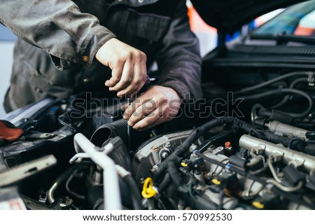 Auto mechanic repairing car. Selective focus. Royalty-Free Stock Photo #570992530
