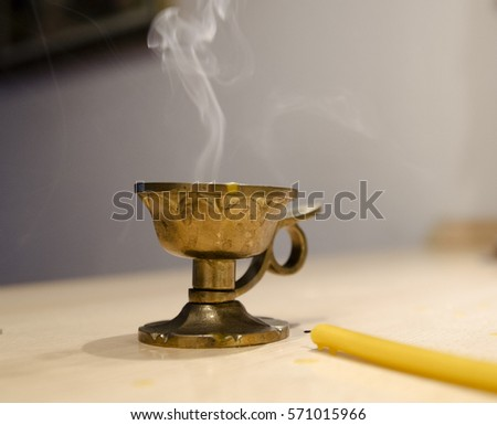 Small Candle golden lamp frankincense burner. Smoke from the briquette and candle. Christian religious custom and aroma therapy. #571015966