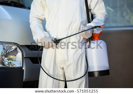 Mid section of pest control man standing next to a van on a street #571051255