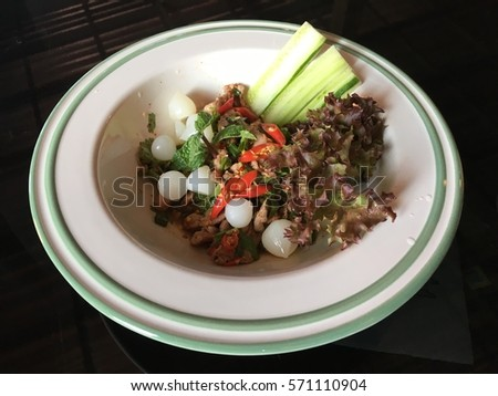 Salad grilled pork with elephant garlic in  white plate on glass table #571110904