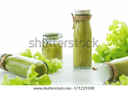 Mix green fruit and vegetable juice made from kiwi & green lettuce in glasses bottle wrapped by hemp rope laying on white table, raw organic fruit juice for healthy people, green juice for weight loss #571229308