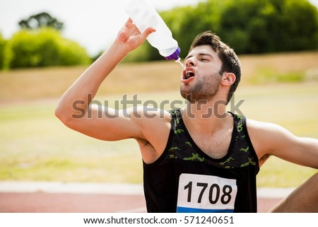 Tired athlete sitting on the running track and drinking water on a sunny day #571240651