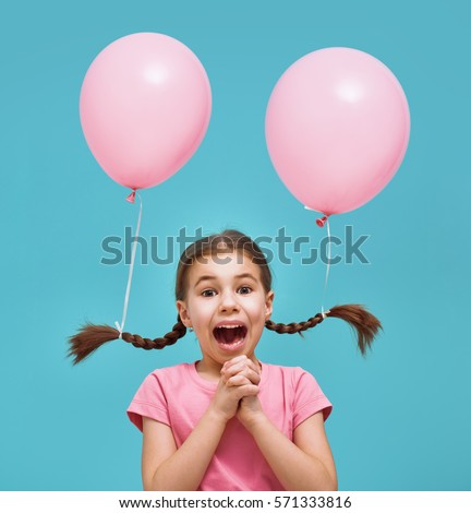 Funny child on a background of bright blue wall. Girl is having fun with balloons. Pink and turquoise colors.