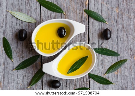 Olive oil with olive leaves on wooden table #571508704
