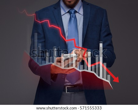 Businessman with chart in the fall, economy going down. Royalty-Free Stock Photo #571555333