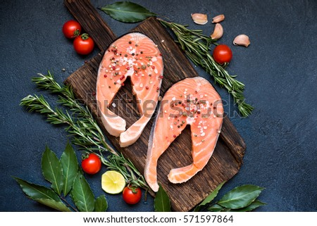 Fresh raw salmon steaks on wooden cutting board with rosemary, top view #571597864
