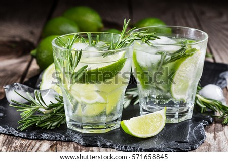 drink with fresh lime and rosemary on a wooden background #571658845
