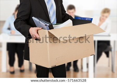 Close-up Of A Businessperson Carrying Cardboard Box During Office Meeting