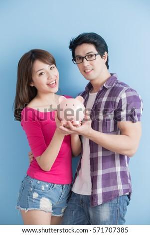 young couple hold pink pig bank and smile happily isolated on blue background #571707385