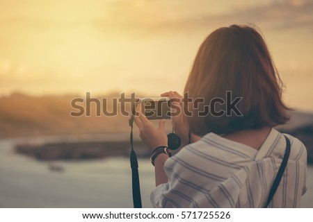female traveler photographing mountain and sea. #571725526