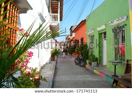 Woman at a street of the neighborhood of Getsemani, in the beautiful colonial city of Cartagena de Indias, Colombia #571745113