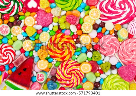 Colorful lollipops and different colored round candy. Top view. Royalty-Free Stock Photo #571790401