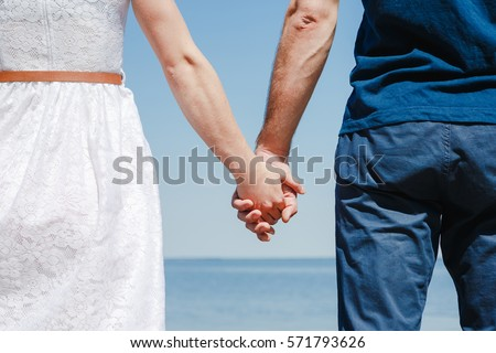 Close up of loving couple holding hands on a beach near the sea #571793626