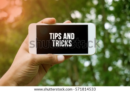 TIPS AND TRICKS word on smartphone with bokeh in background