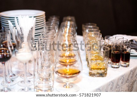 Glasses with different kinds of alcohol stand served in rows on dinner table #571821907