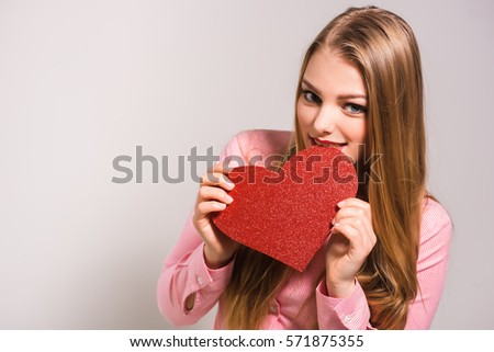 Portrait of a young smiling blonde girl with red lips wearing shirt and biting cartoon heart. White background. Valentine's Day, Christmas, Birthday, Holidays.