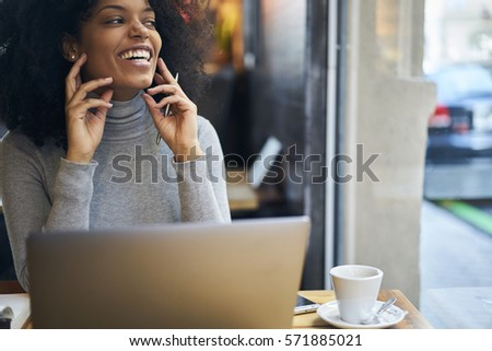 Cheerful female CEO feeling excited about finishing project for outsource and signing beneficial contract via internet communication chat using wireless connection to fast internet in cafe wifi zone #571885021