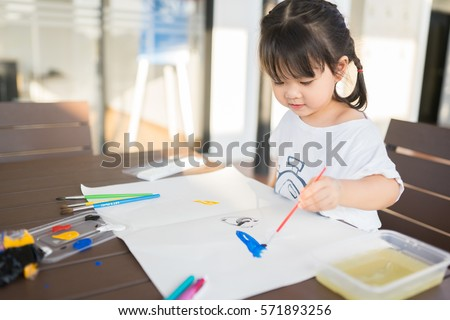 little asian girl painting with paintbrush and colorful paints