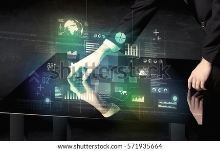 Businessman touching interactive modern desk with technology icons on table Royalty-Free Stock Photo #571935664
