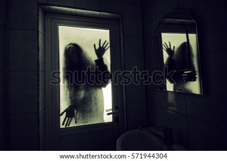 Horror woman in window wood hand hold cage scary scene halloween concept Blurred silhouette of witch Royalty-Free Stock Photo #571944304